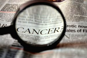 Cancer-Magnified-in-Newspaper-FoterDotCom